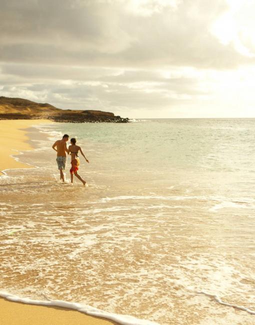 A couple walking on an empty beach on Molokai