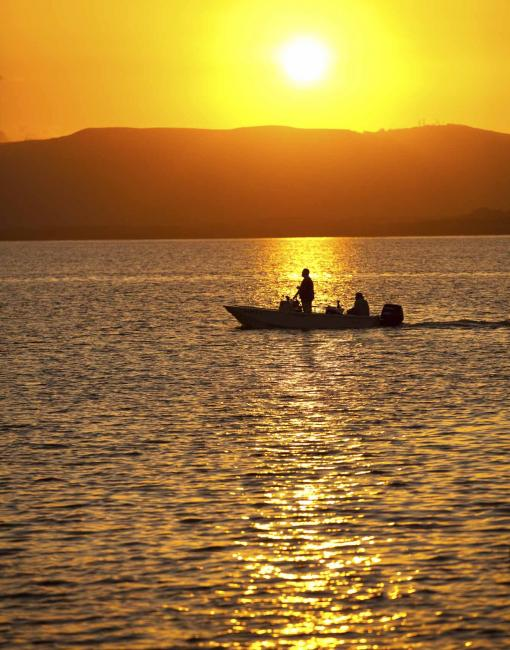 A person in a boat off the island of Molokai at sunset