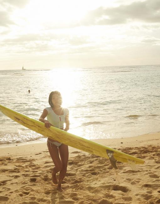 A woman carries a surfboard out of the water as the sunsets