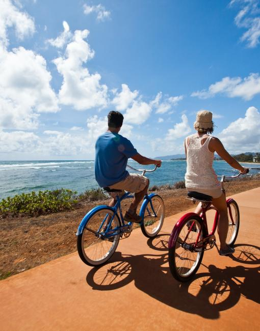 A couple riding bikes in Kapaa Town, Kauai