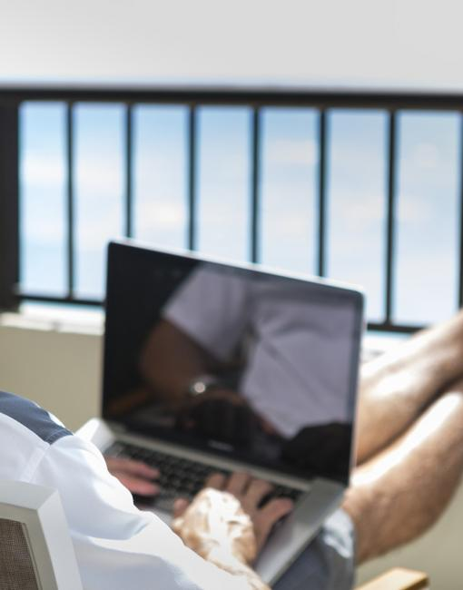 A man working on his computer with an ocean view