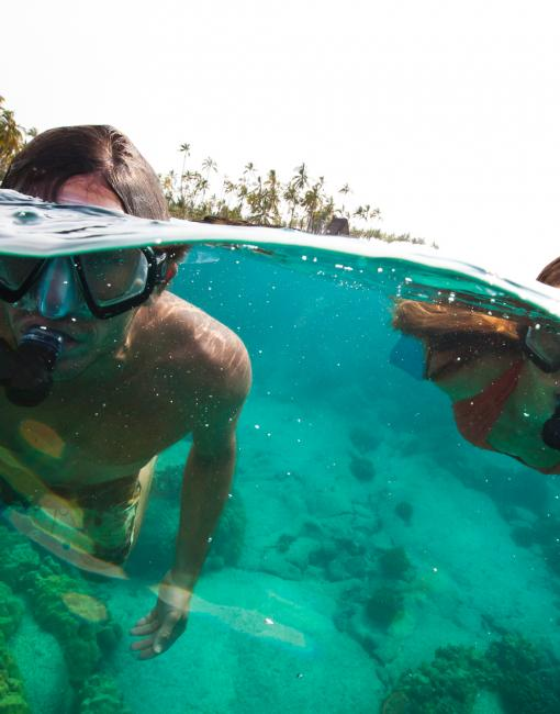 A father and son snorkel through bright blue water