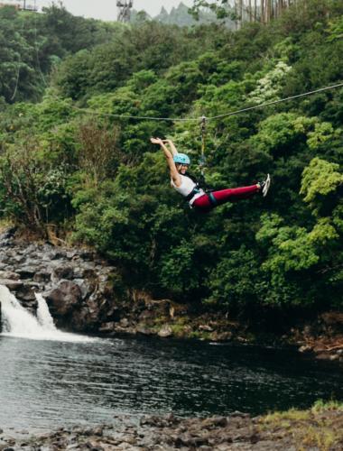 A woman ziplines over a waterfall on the Island of Hawaii.