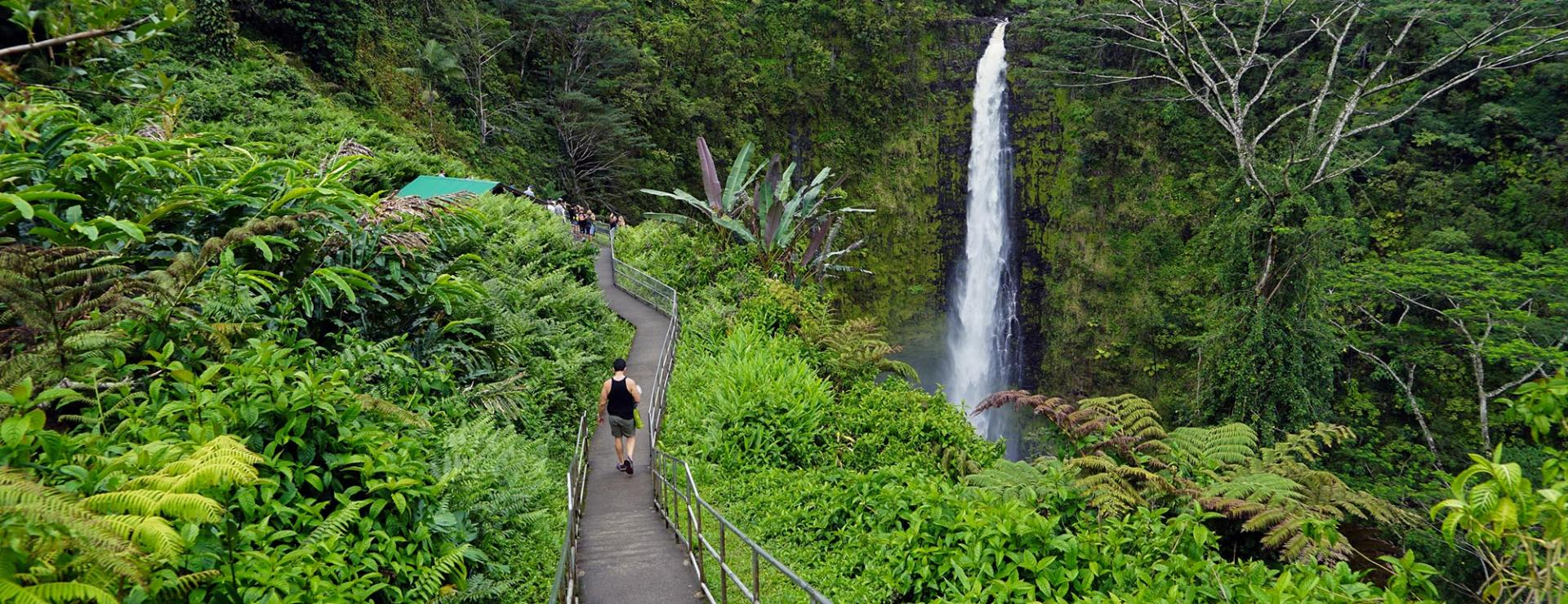Woman hiking by waterful in Hawaii