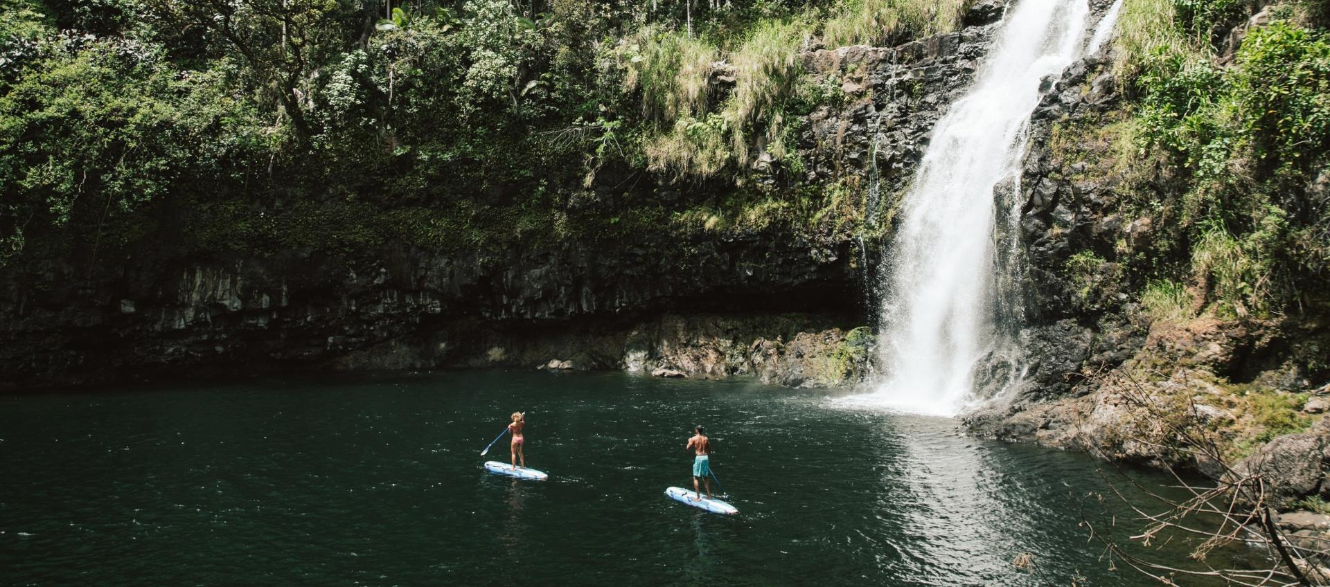 Couple paddleboards below Kulaniapia Falls