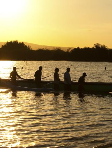 Outrigger canoeing at sunset off the Hawaiian island of Molokai