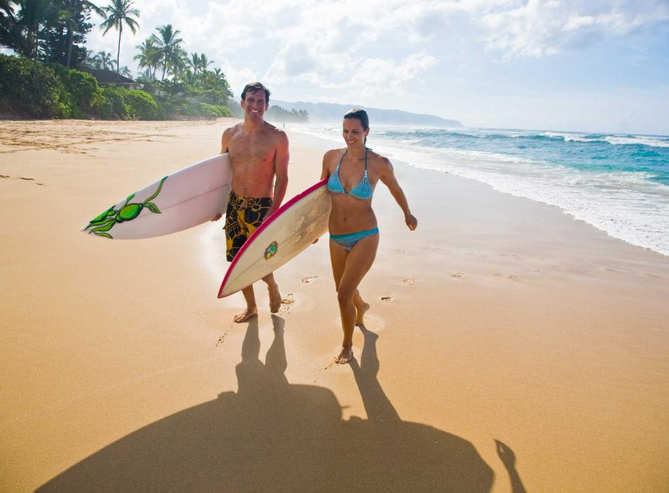 Couple with surfboards on a beach in Oahu